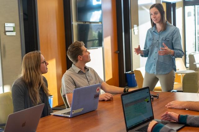 plusieurs personnes assises devant des ordinateurs en réunion